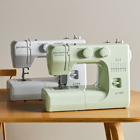 Two sewing machines side by side on table