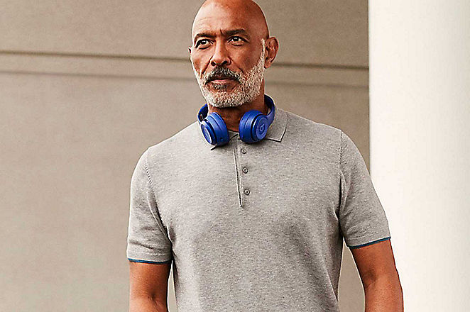 Man wearing grey polo shirt with headphones round neck