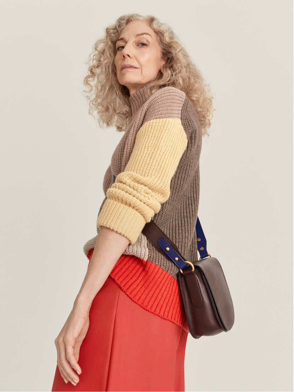 Model wearing a block colour jumper and red skirt