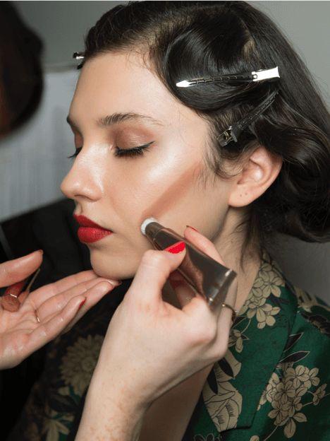Charlotte Tilbury applying bronzer to model backstage at Alice Temperley LFW