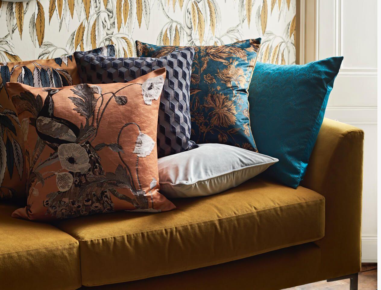 Patterned cushions on a velvet sofa