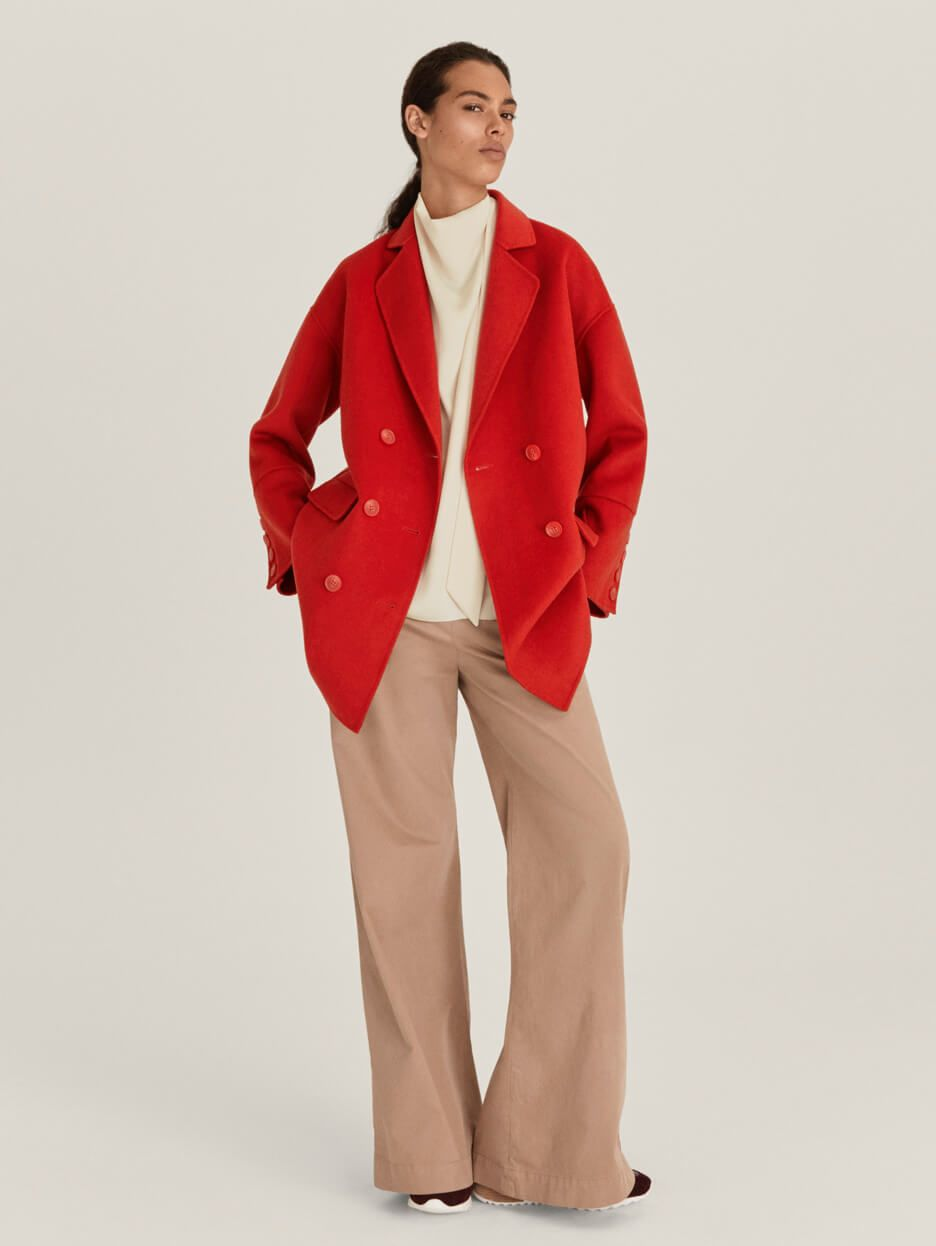 Model wearing a red coat and neutral trousers