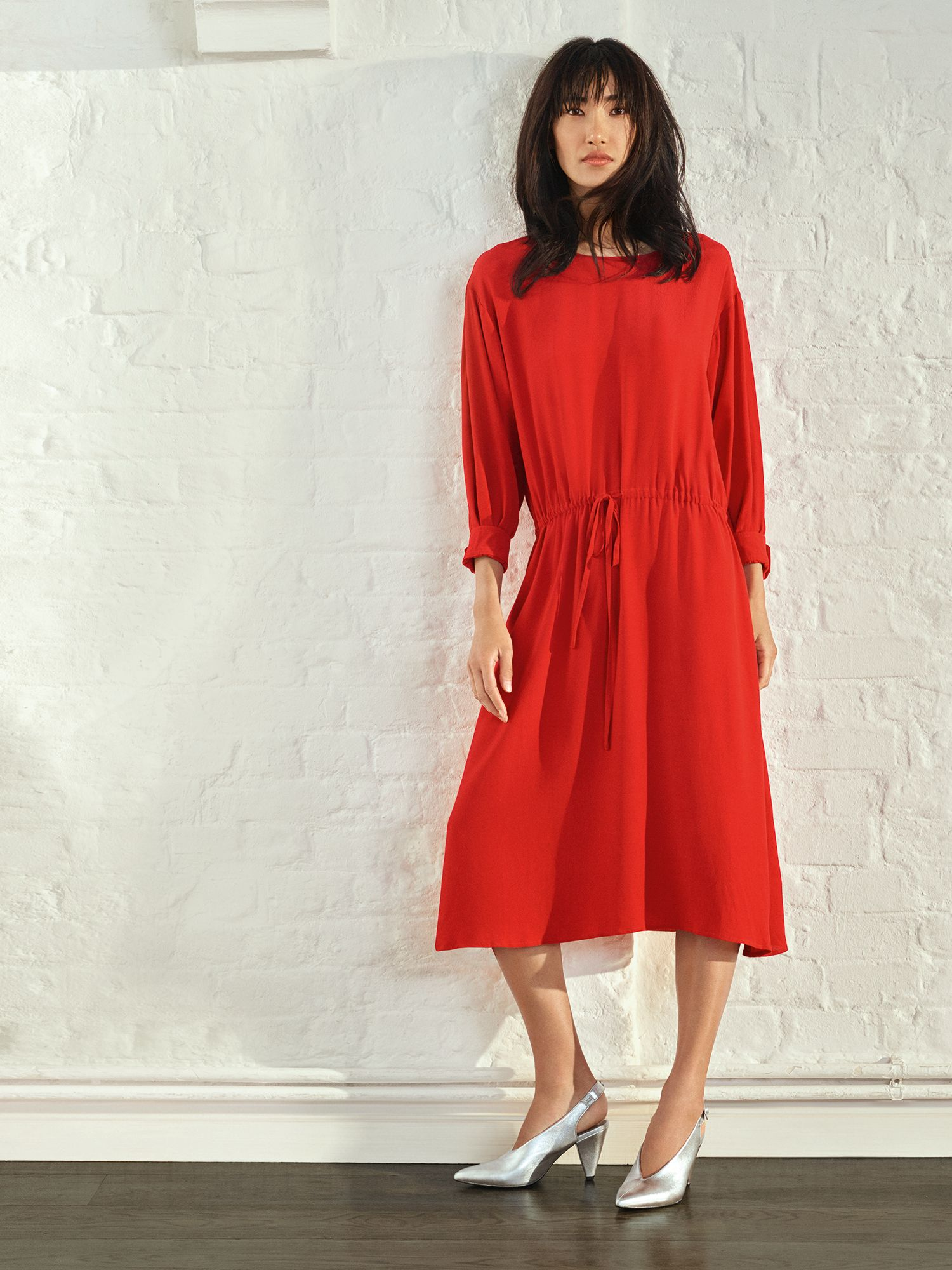 A model wearing a red dress and silver cone-heel shoes from fashion retailer John Lewis