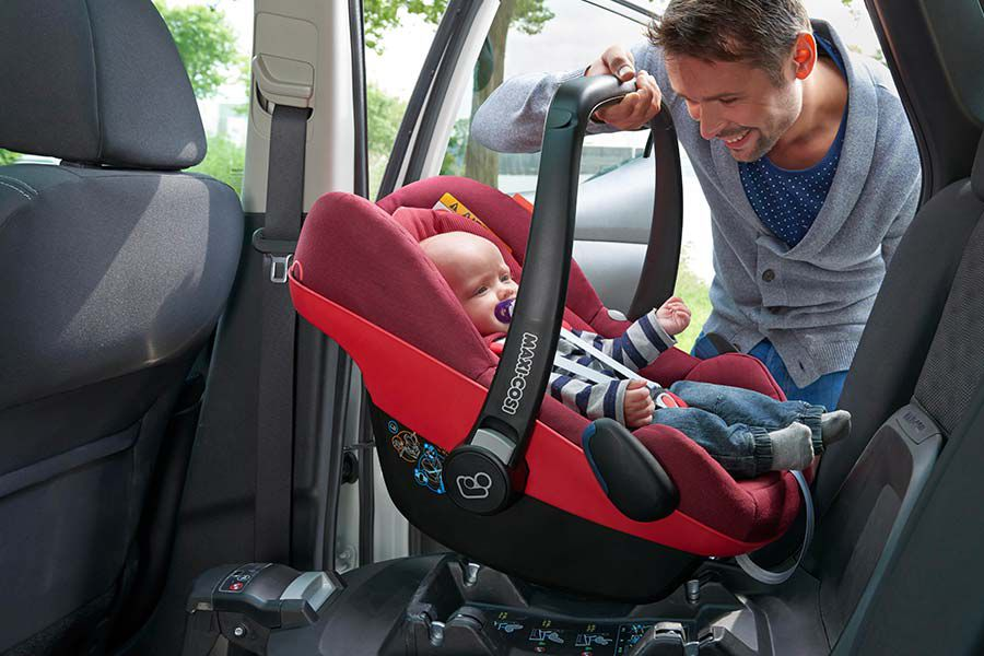 Man securing car seat in car