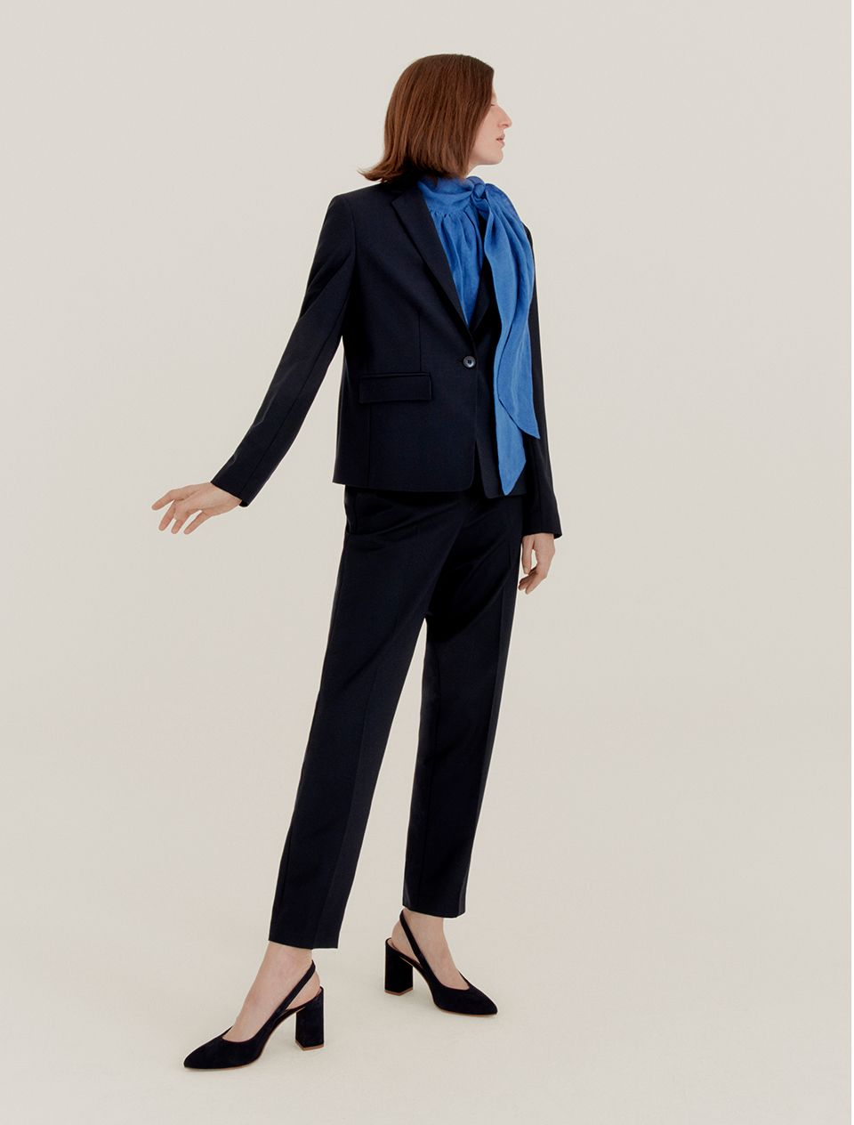 Woman in a black suit and blue blouse