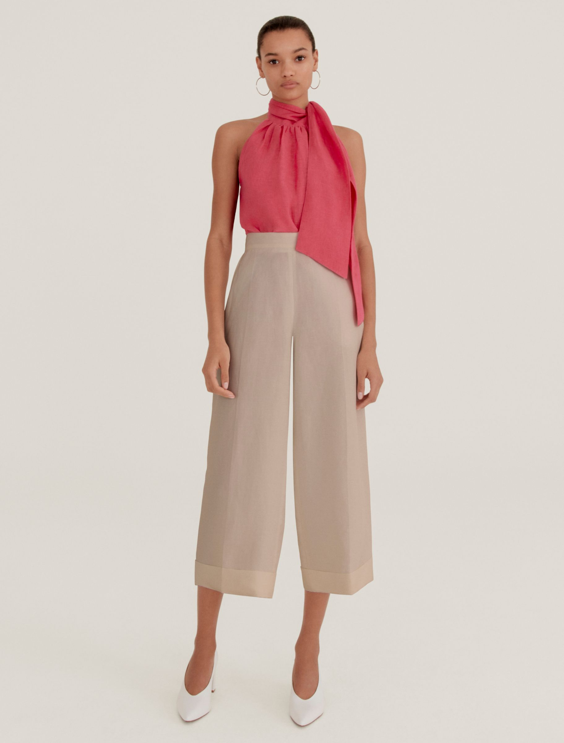 Woman in pink blouse and neutral trousers