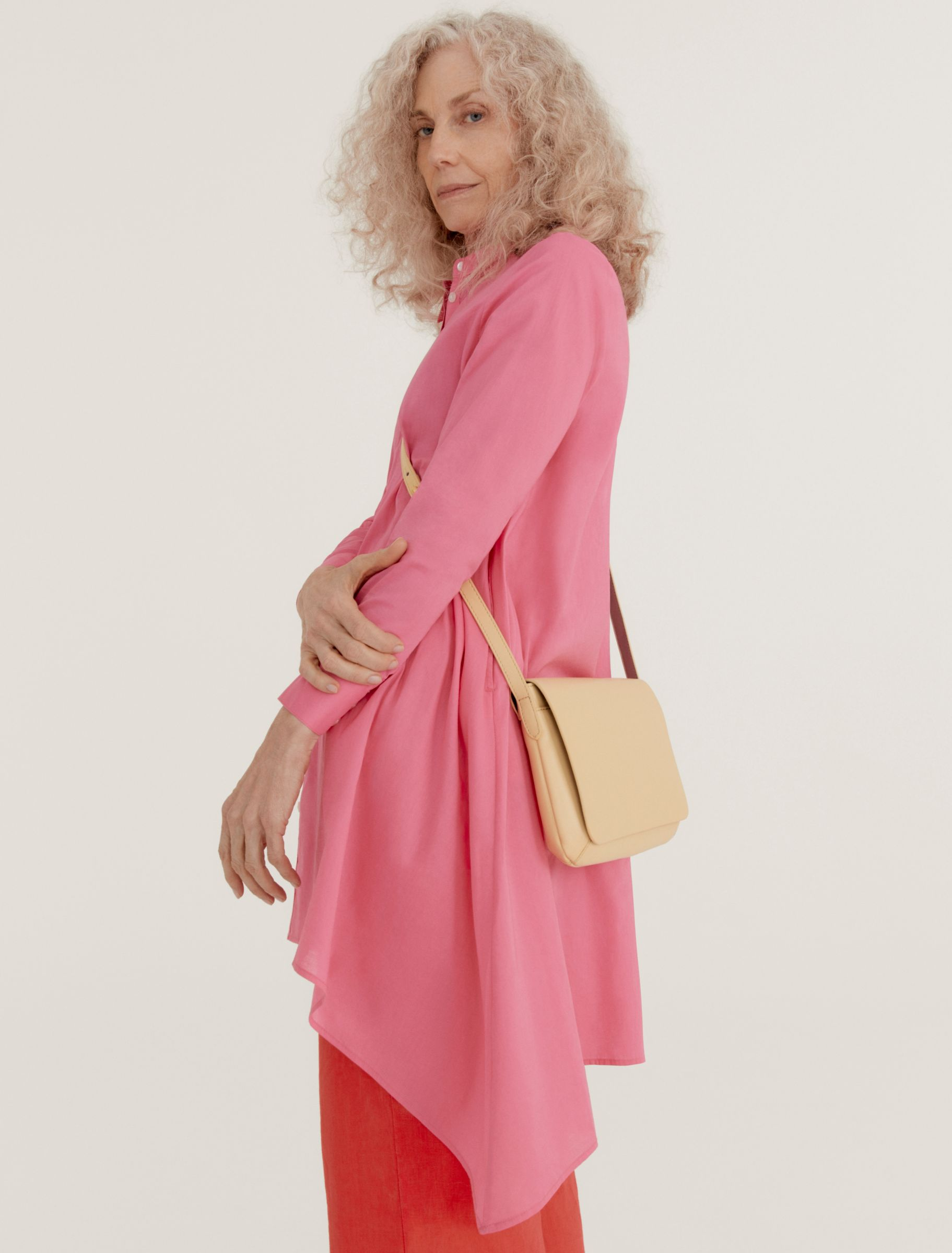 Woman wearing pink shirt and red trousers