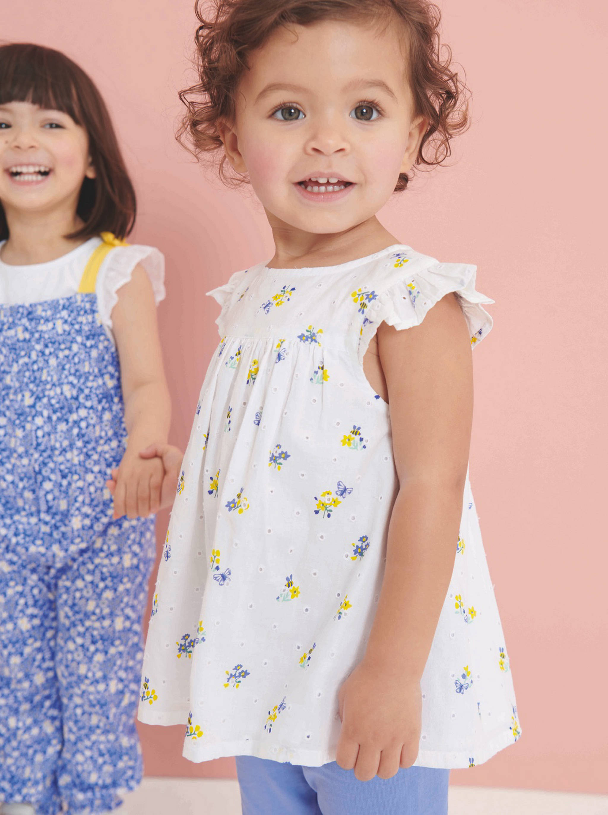 A little girl dressed in a white top with yellow flowers and blue trousers