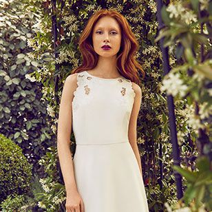 Woman wearing white dress in garden setting