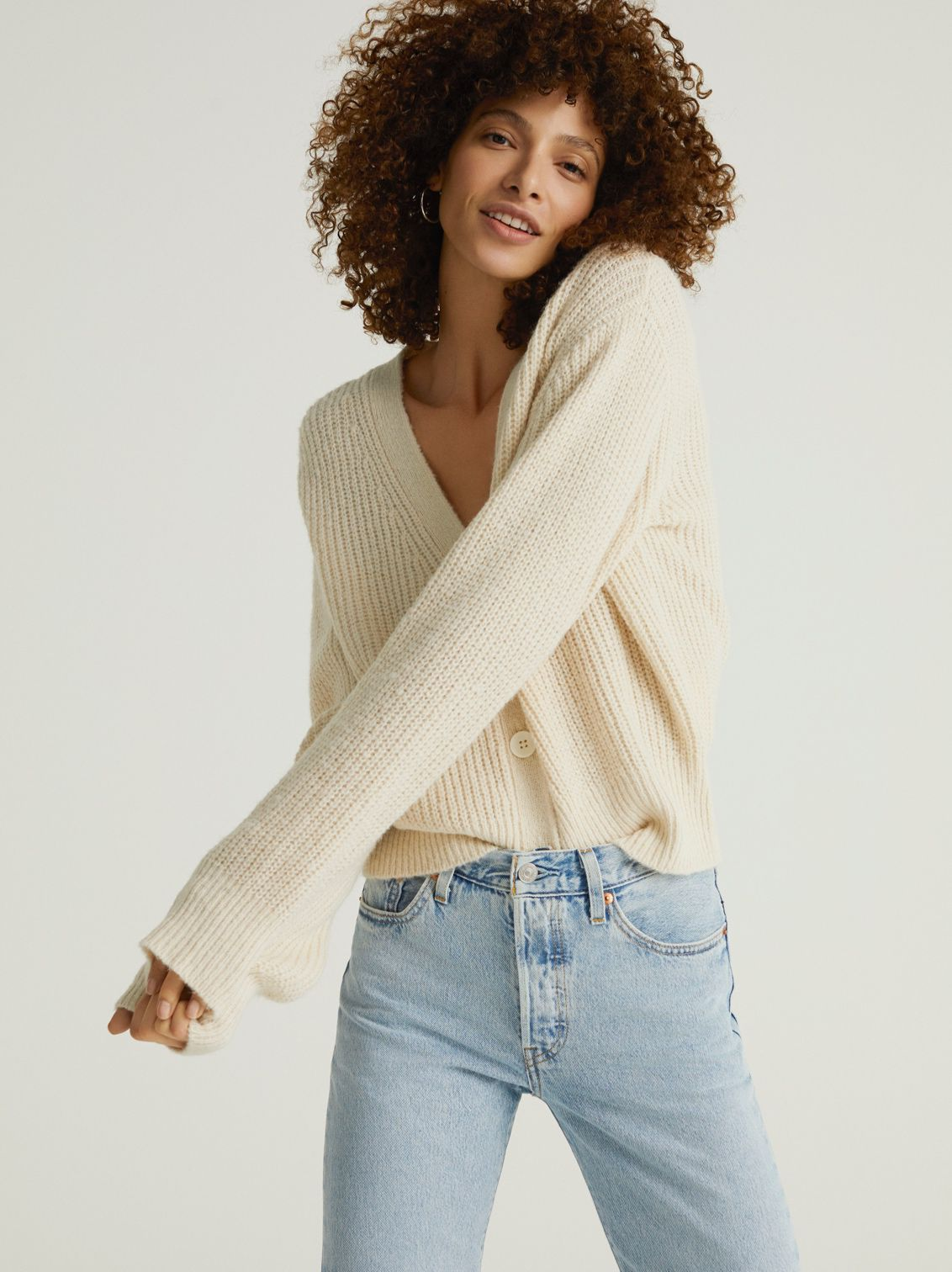 Woman standing in an And/or cream cardigan and Levi jeans