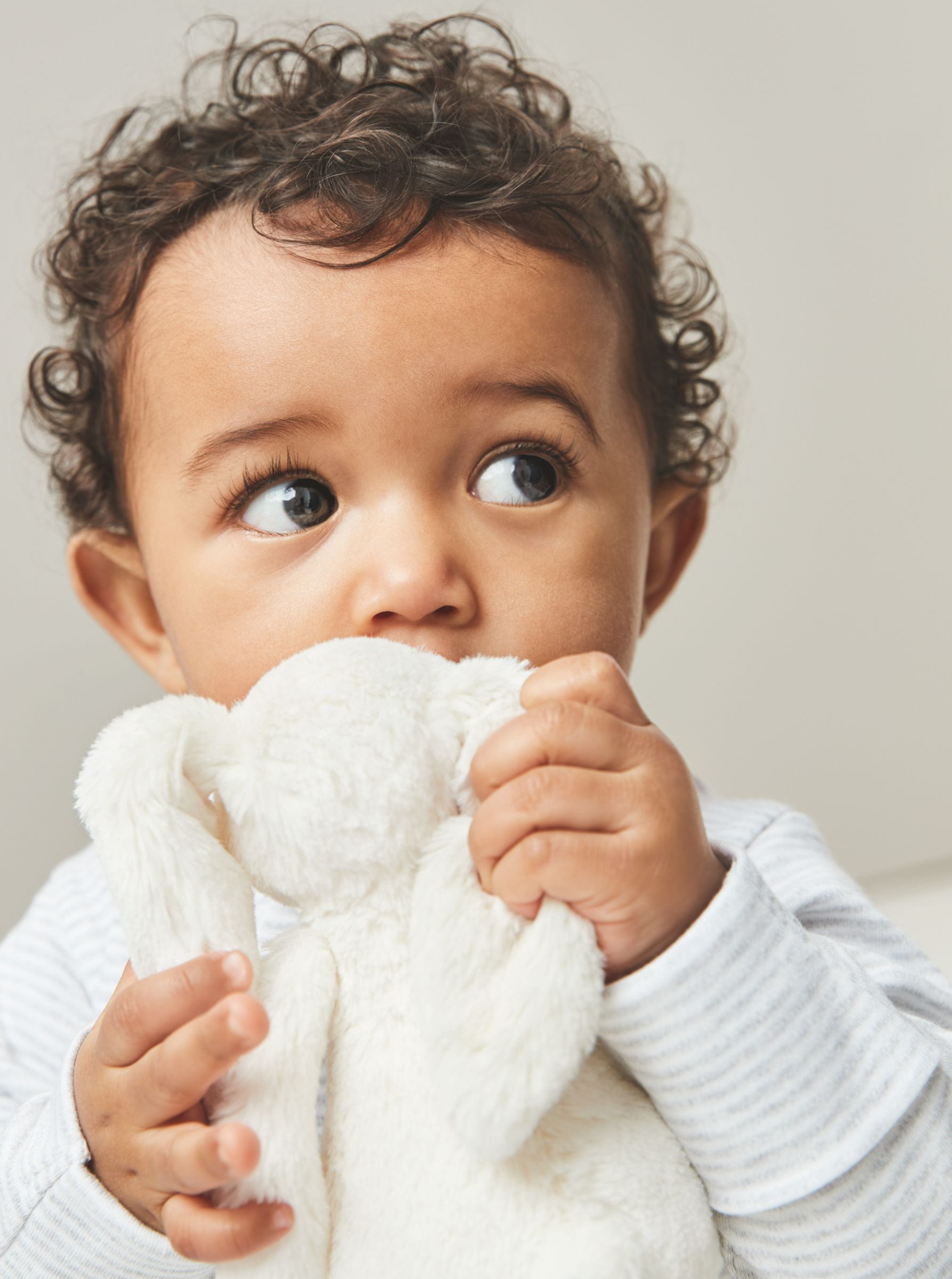 Baby holding a cuddly toy on a grey background