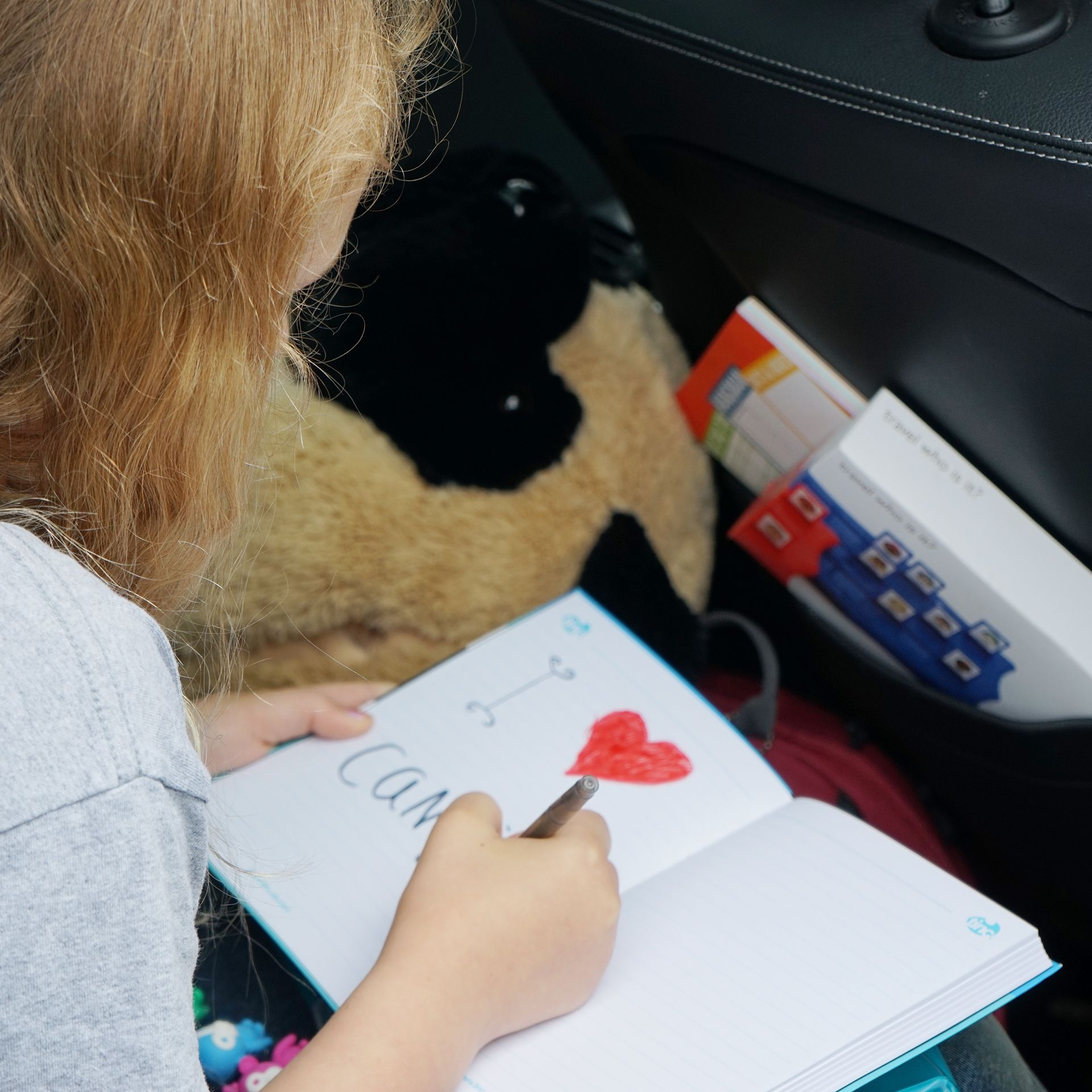 Girl in a car with a sketch pad