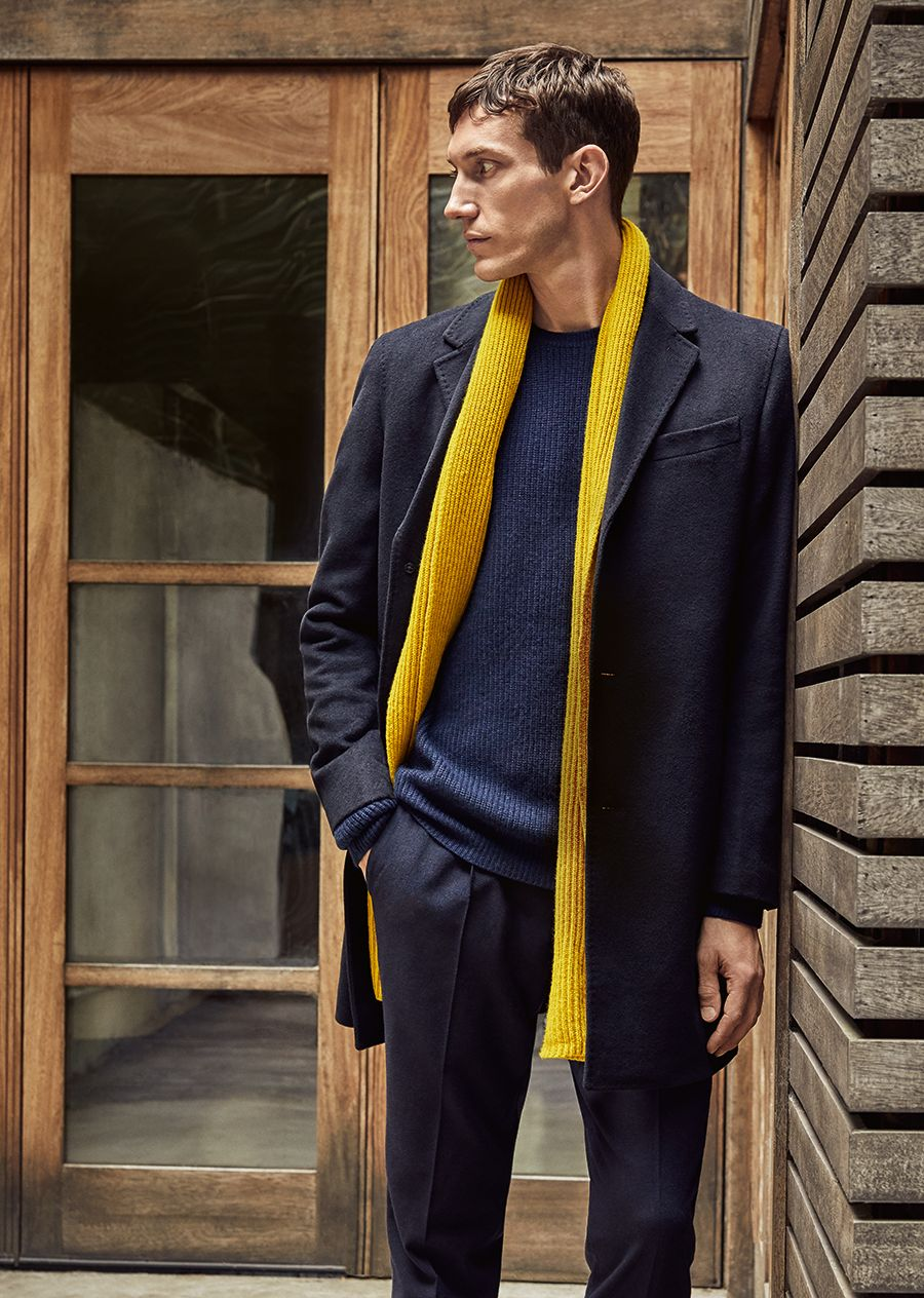 Model in blue overcoat and yellow scarf