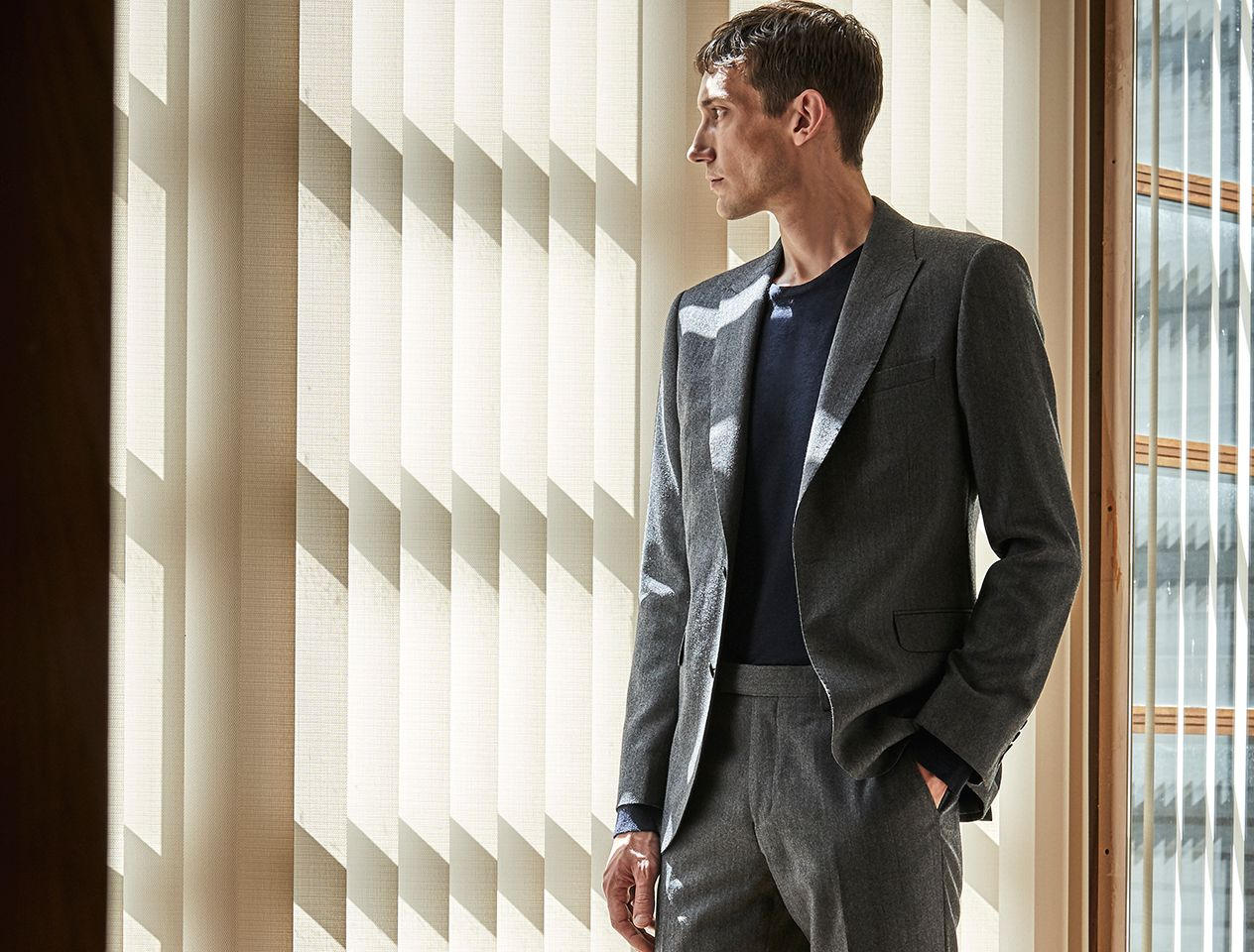 A model wearing a suit - one of the key pieces that make up a men's capsule wardrobe