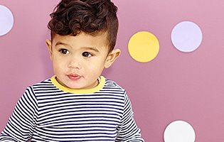 Male toddler against a polka-dot wall
