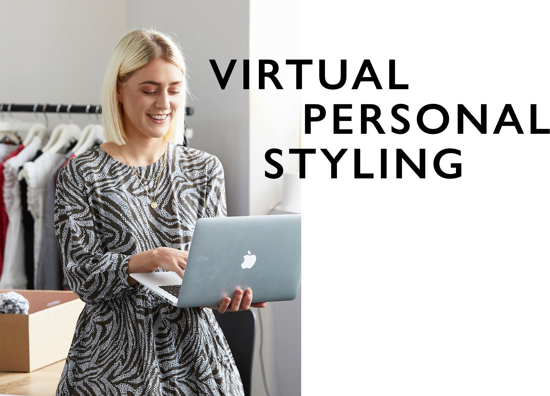 A Personal Stylist surrounded by clothing holding her laptop