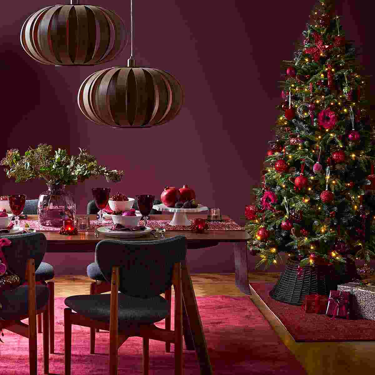 Beautiful plum-coloured dining room; with fully laid table and tree