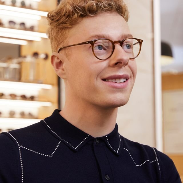 man standing in an opticians wearing glasses