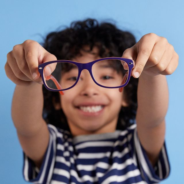 Boy out of focus on a blue background holding up glasses in focus