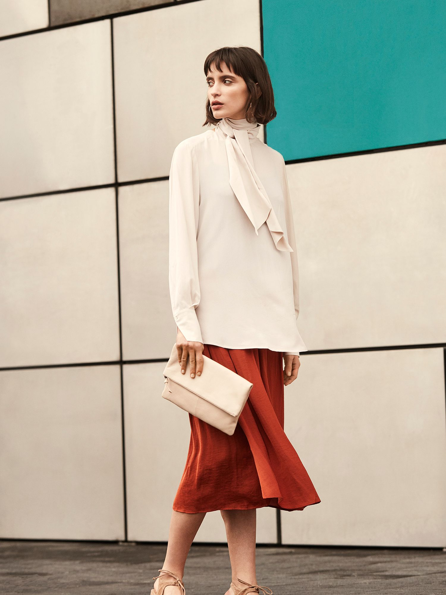 woman wearing a white blouse and satin skirt