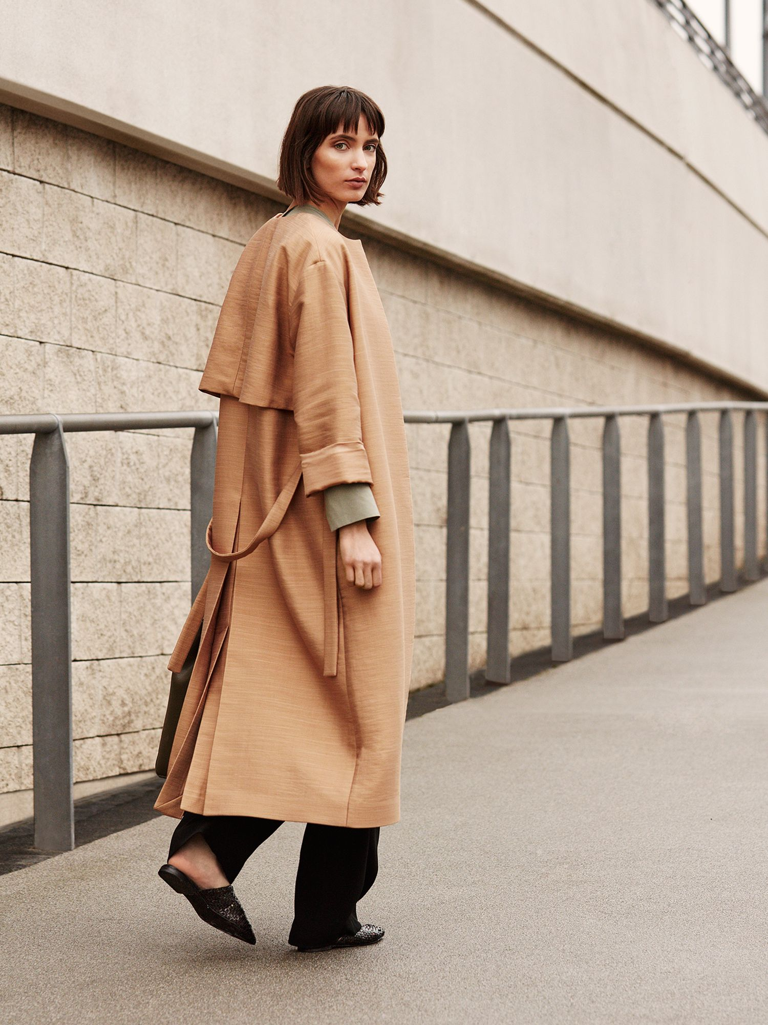 woman in a trench coat and flat shoes