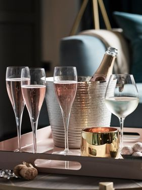 Champagne flutes alongside bottle in bucket