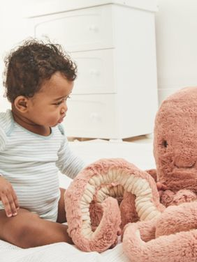 Baby playing with octopus plush toy