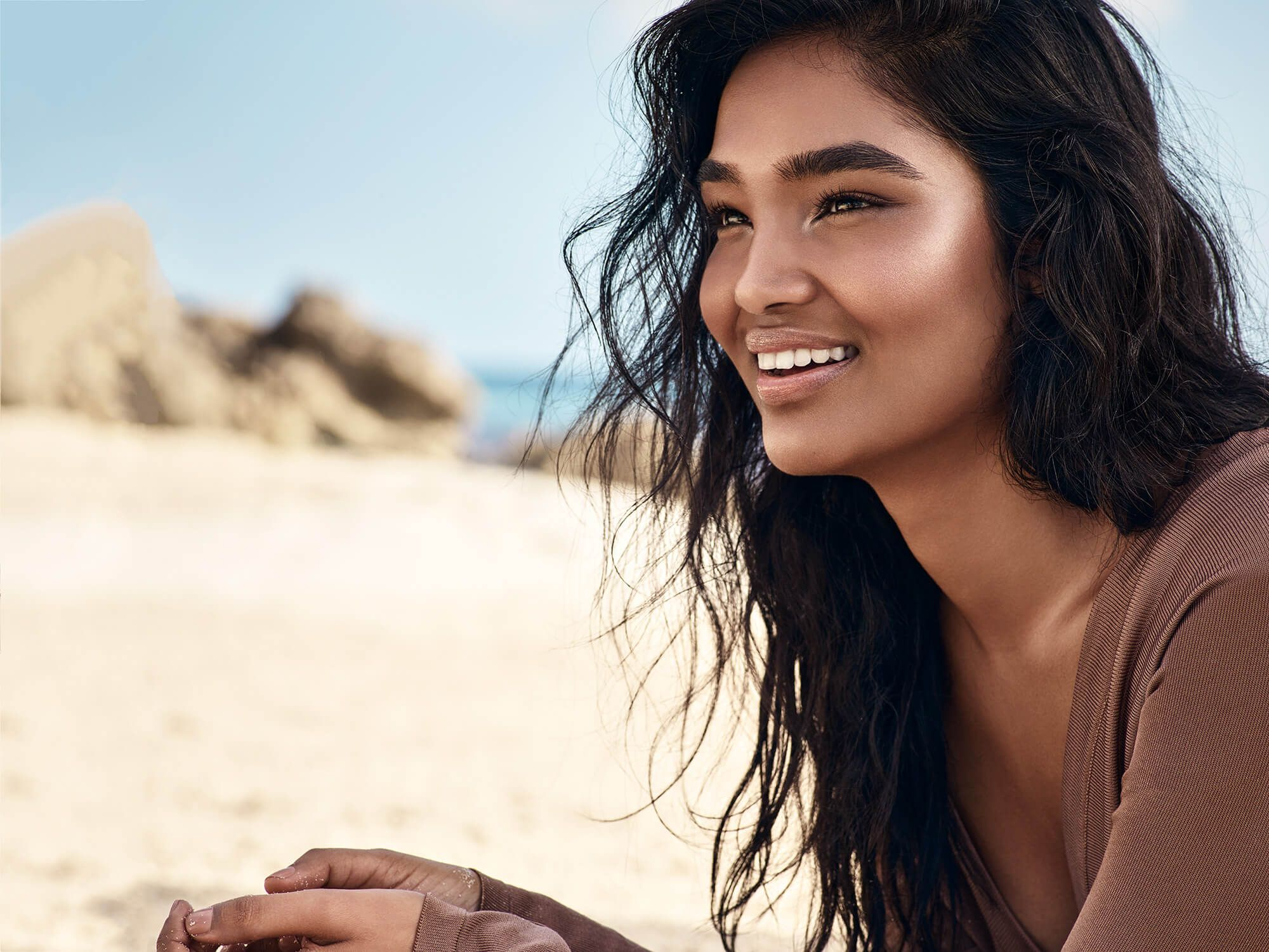 Model smiling on sandy beach