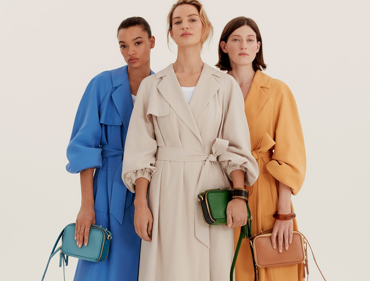Models wearing blue, yellow and stone trench coats