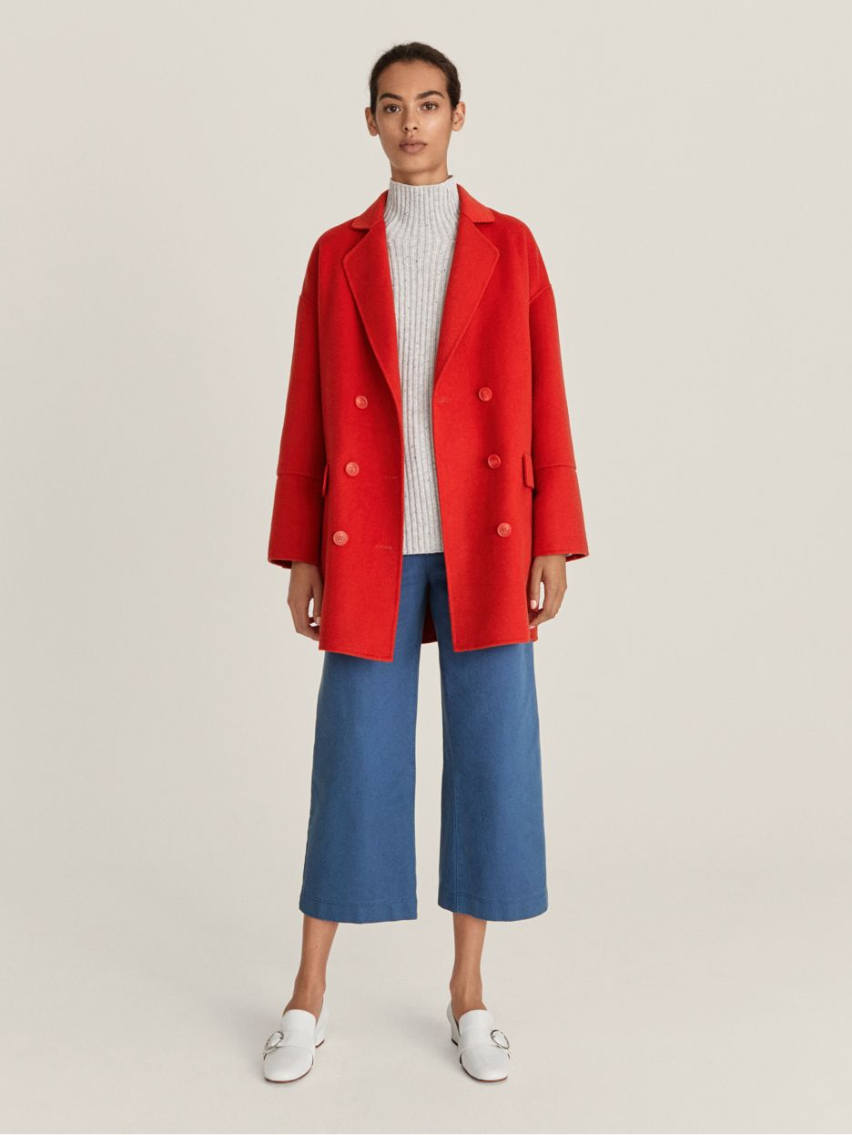 Model wearing red coat and blue wide-leg cropped trousers