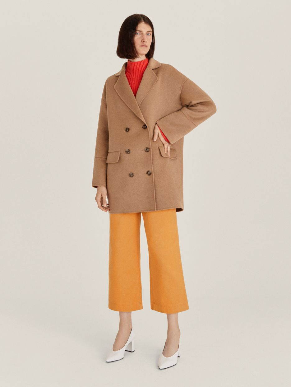 Model wearing camel coat and mustard wide-legged cropped trousers