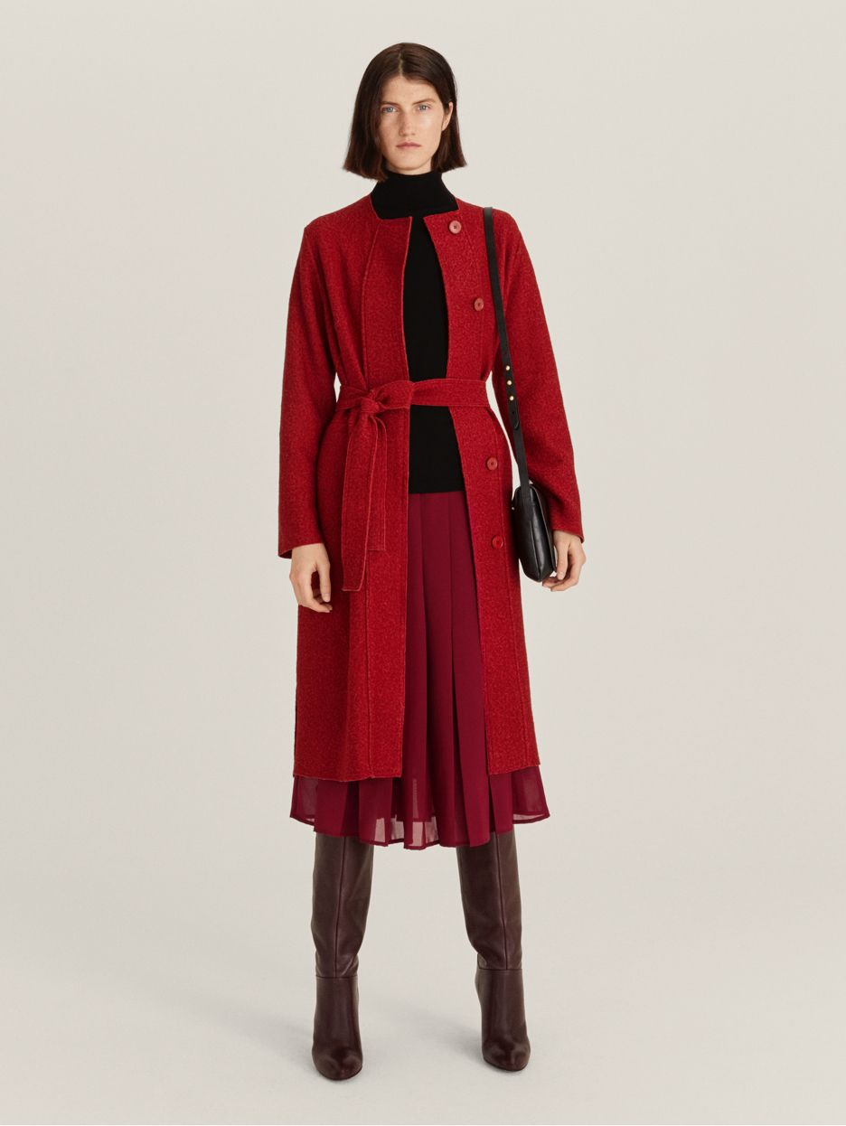 Model wearing red coat and pleated skirt
