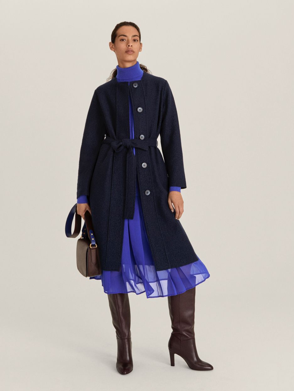 Model wearing blue coat and pleated sheer skirt