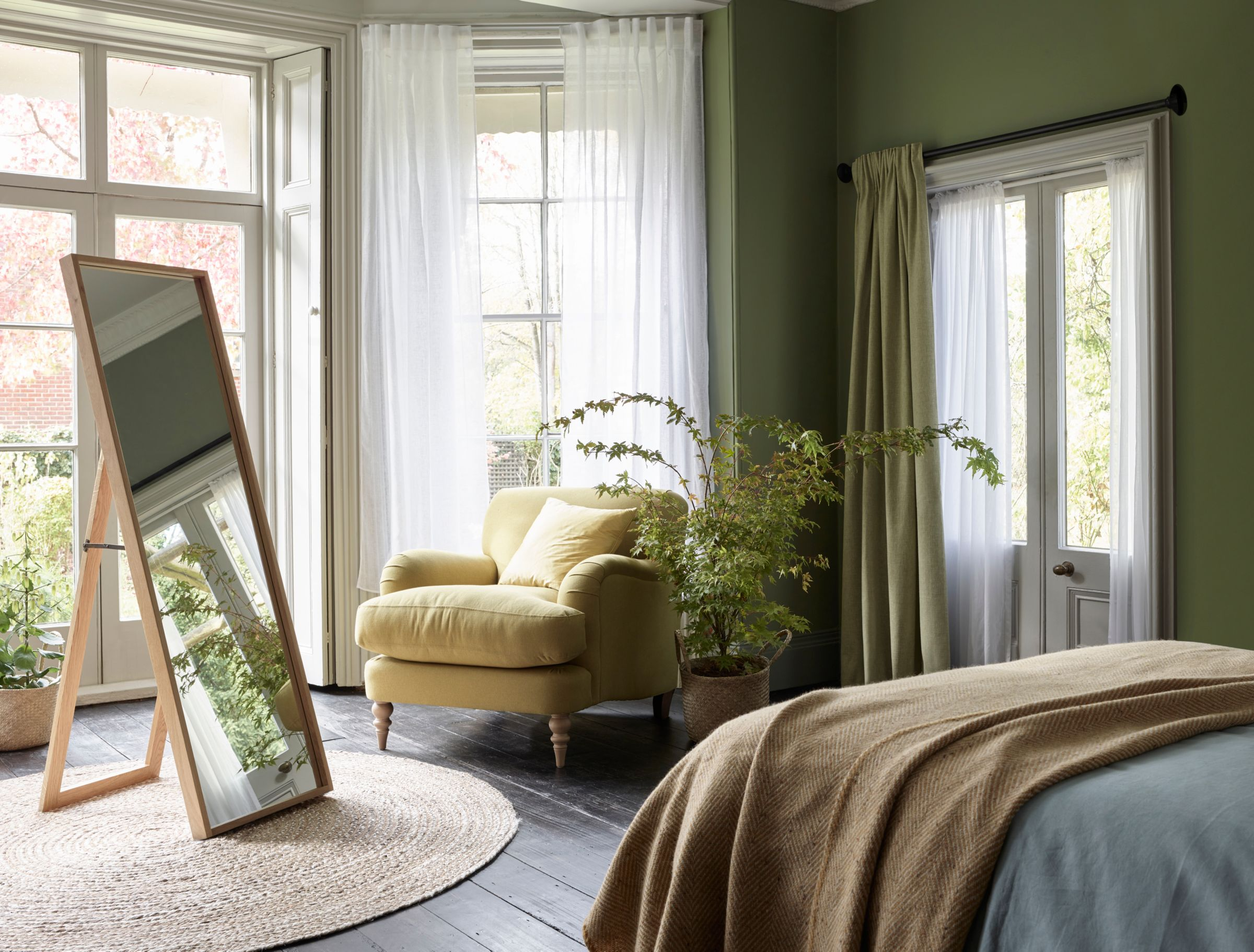 Green bedroom with wood frame mirror