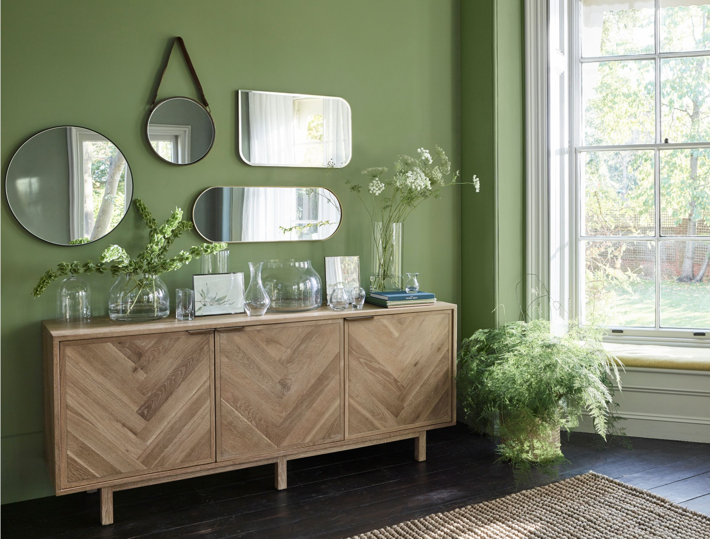 Green wall with mirrors and wooden cabinet