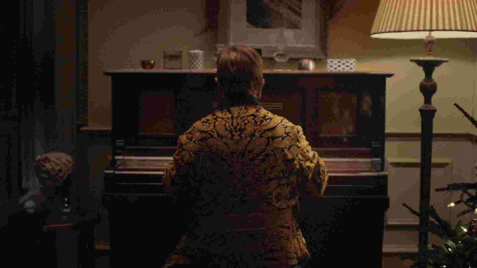 Sir Elton John, sitting at his first piano in a darkened Christmas-decorated sitting room